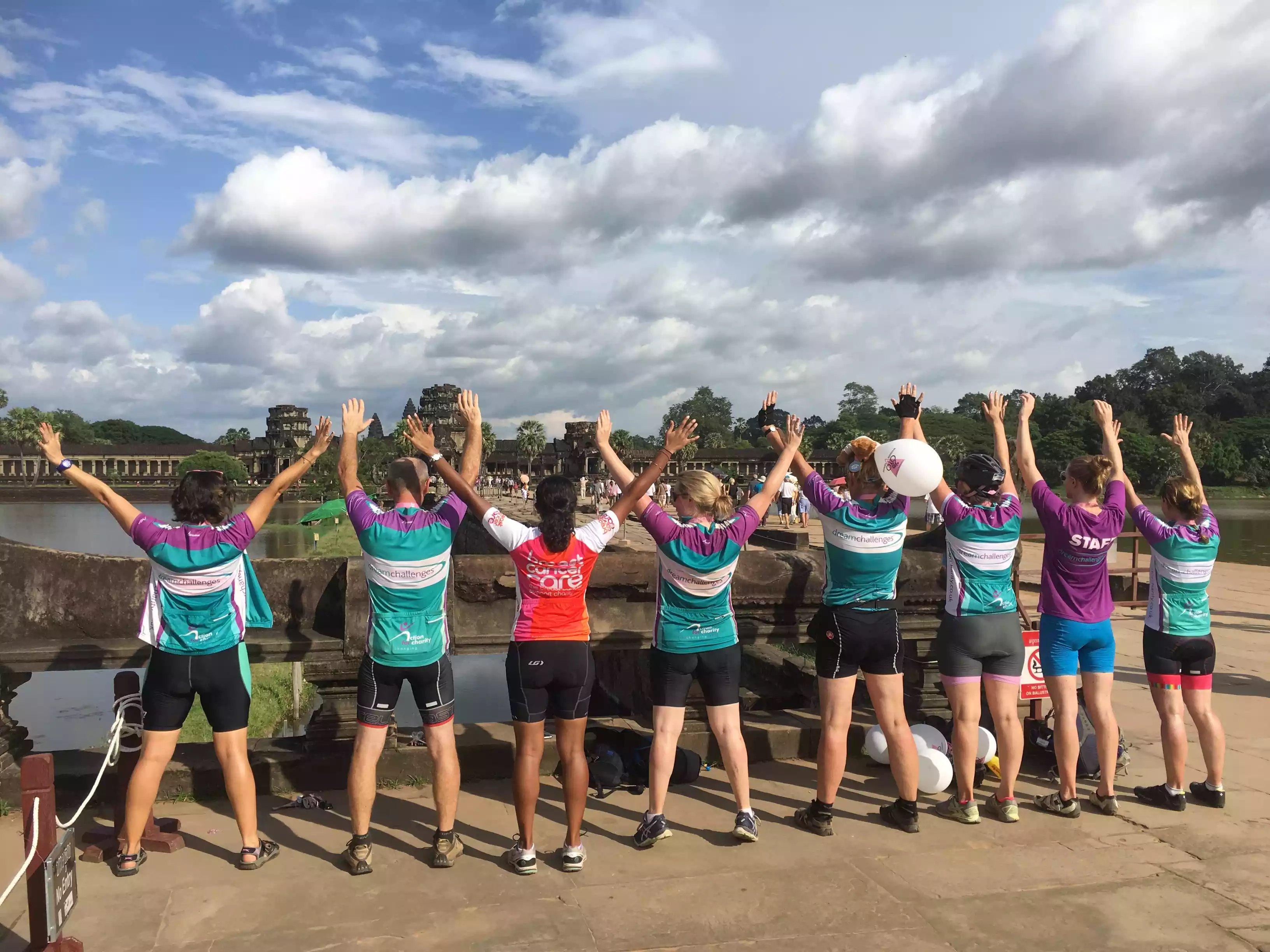 Staff cheer in front of Angkor Wat